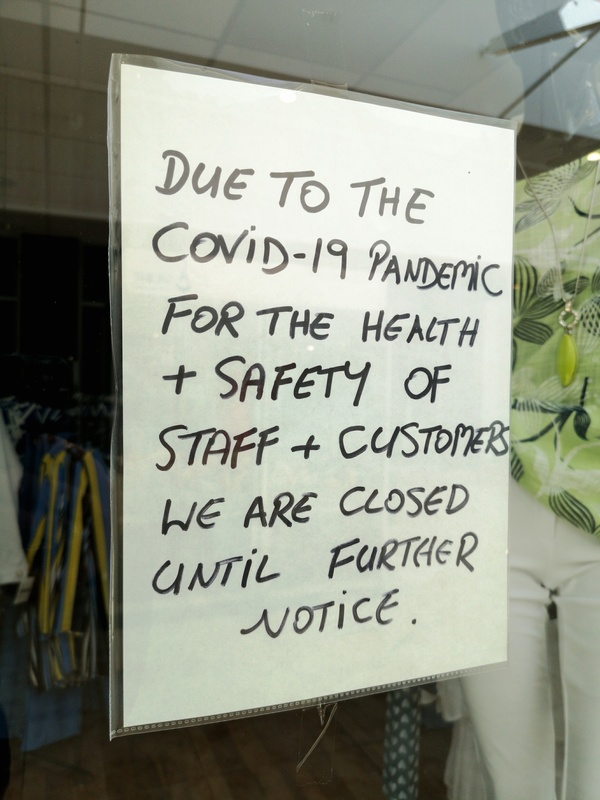 A sign in a shop window saying the shop is closed until further notice due to COVID-19