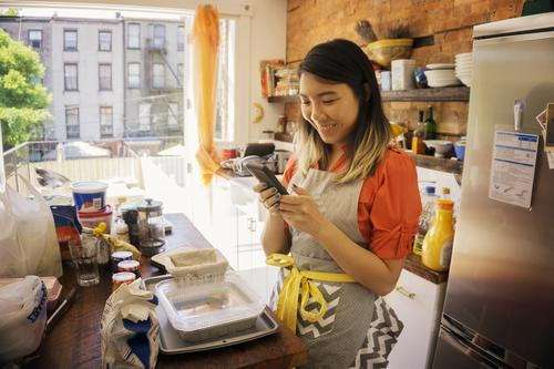 woman smiling on phone while cooking in kitchen